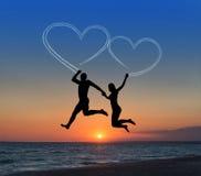 Houdend van paar die het vliegen hemel tegen hart-vormige overzees beachand Royalty-vrije Stock Fotografie