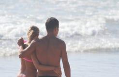 Houdend van paar die langs de kust, mening van de rug lopen royalty-vrije stock afbeelding