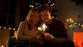 Houdend van paar die met de lichten van Bengalen dichtbij Kerstmisboom zitten, die wens in Nieuwjaar maken royalty-vrije stock fotografie