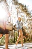 Houdend van paar die met skateboards in openlucht lopen Opzij het kijken royalty-vrije stock afbeeldingen