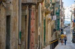 Houdend van paar die onderaan de straat in Valletta, Malta lopen, Stock Foto's