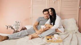 Houdend van paar die ontbijt in bed op de Dag van Valentine in langzame motie hebben stock video