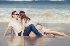 Houdend van paar die op het strand in de dagtijd liggen Stock Afbeelding