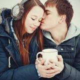 Houdend van paar die in warme kleren hete drank in openlucht drinken stock fotografie