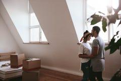 Houdend van paar die zich in hun nieuw huis bewegen royalty-vrije stock fotografie