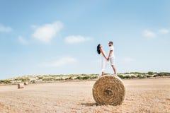 Houdend van paar die zich op een hooiberg bevinden en aan elkaar glimlachen royalty-vrije stock afbeeldingen