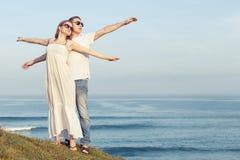 Houdend van paar die zich op het strand in de dagtijd bevinden Royalty-vrije Stock Fotografie