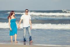 Houdend van paar die zich op het strand in de dagtijd bevinden Royalty-vrije Stock Afbeelding