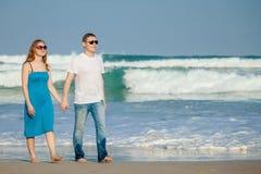 Houdend van paar die zich op het strand in de dagtijd bevinden Royalty-vrije Stock Foto's
