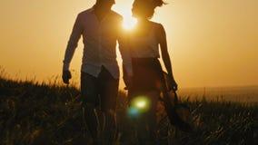 Houdend van paar - moedige jonge mens en mooi meisje bij zonsondergangsilhouet, stock footage