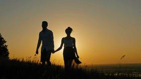 Houdend van paar - moedige jonge mens en mooi meisje bij zonsondergangsilhouet stock videobeelden