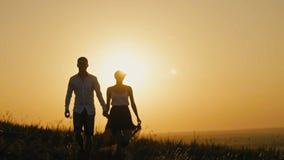 Houdend van paar - moedige jonge mens en mooi meisje bij zonsondergangsilhouet, over de zon stock videobeelden