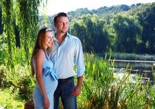 Houdend van paar op de rivierkust Stock Fotografie