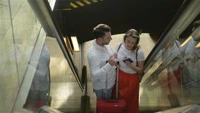Houdend van paar op de roltrap bij de luchthaven Een kerel en zijn meisje reizen samen Mensen met Kaukasisch stock video