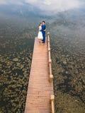 Houdend van paar op het dok bij het meer stock afbeeldingen