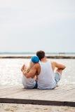 Houdend van paar op het strand die terwijl op zee het kijken koesteren Stock Foto