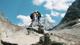 Houdend van paar van toeristen met rugzakken in de stijgingskus op de bovenkant in de bergen Het concept liefde, voltooiing royalty-vrije stock afbeelding
