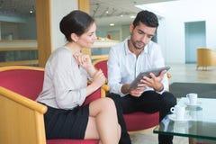 Houdend van paar in vrijetijdskleding die tabletcomputer met behulp van terwijl het wachten royalty-vrije stock fotografie