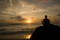 Houdend zon - jonge mens het mediteren op het strand royalty-vrije stock afbeeldingen