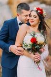 Houdende van bruidegom die zijn vrij nieuwe vrouw op de wang in het platteland kussen Haar van lichte wind het klappende vrouwen  royalty-vrije stock fotografie