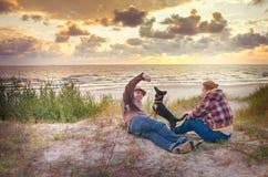 Houdende van familie bij zonsondergangoverzees Stock Afbeeldingen