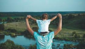 Houdende van familie Vader en zijn jongen die en van de zoonsbaby in openlucht spelen koesteren Gelukkige papa en zoon in openluc stock fotografie