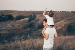 Houdende van familie Vader en zijn jongen die en van de zoonsbaby in openlucht spelen koesteren Gelukkige papa en zoon in openluc royalty-vrije stock foto