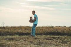 Houdende van familie Vader en zijn jongen die en van de zoonsbaby in openlucht spelen koesteren Gelukkige papa en zoon in openluc royalty-vrije stock fotografie