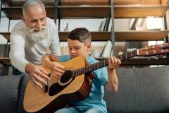 Houdende van grootvader en kleinzoon die gitaarpraktijk hebben stock afbeeldingen
