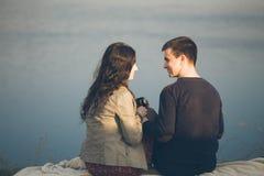Houdende van jonge paar gelukkige samen openlucht, het drinken thee Een kerel met een meisje op het meer bij zonsondergang drinkt Royalty-vrije Stock Fotografie