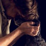 Houdende van mens die zijn terriërhond koesteren Stock Foto