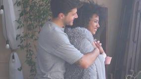 Houdende van mens die zijn vrouw omvatten met warme deken terwijl het hebben van koffie stock footage