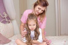 Houdende van moeder die haar droevige en nukkige dochter troosten stock foto's