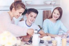 Houdende van moeder die kinderen behandelen tijdens de tijd van het familieontbijt royalty-vrije stock foto