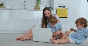 Houdende van moeder en kinderen die en pret speelzitting op de vloer koesteren hebben Pret en gelukkige familie Het spel daarna stock video