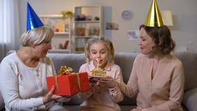 Houdende van moeder en oma die leuk meisje gelukwensen die met verjaardag, kaars blazen stock videobeelden