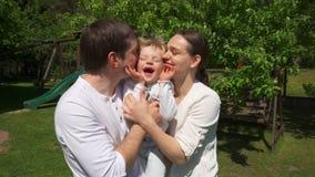 Houdende van ouders die en leuke jongen in de zomertuin omhelzen kussen Handbediend schot stock video