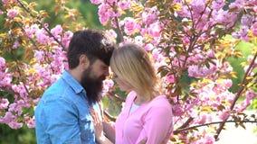Houdende van paar en de lentebloemen Portret van meisje en jongen binnen Mooie aardscène met bloeiende boom en zonnig stock videobeelden