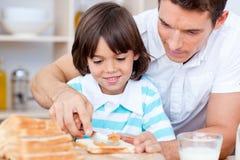 Houdende van vader en zijn zoon het uitspreiden jam op brood stock foto
