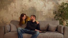 Houdende van vrouw die de bezige mens omhelzen die aan laptop werken stock videobeelden