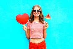 Houdt de manier mooie glimlachende vrouw een rood de vorm en de plakwatermeloenroomijs van het ballonhart Stock Afbeelding