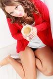 Houdt de meisjes rode sweater mok met koffie Stock Afbeeldingen