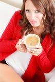 Houdt de meisjes rode sweater mok met koffie Royalty-vrije Stock Fotografie