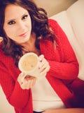Houdt de meisjes rode sweater mok met koffie Royalty-vrije Stock Foto