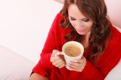 Houdt de meisjes rode sweater mok met koffie Stock Afbeelding
