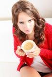 Houdt de meisjes rode sweater mok met koffie Royalty-vrije Stock Foto's