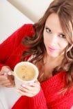 Houdt de meisjes rode sweater mok met koffie Royalty-vrije Stock Afbeeldingen