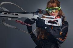 Houdt de vrouwelijke sportmannen van roodharigebiatlon concurrerend kanon stock foto
