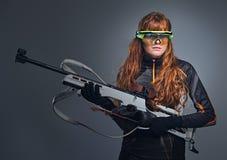 Houdt de vrouwelijke sportmannen van roodharigebiatlon concurrerend kanon royalty-vrije stock afbeeldingen