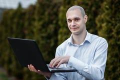 Houdt het mensen witte overhemd laptop op zijn wapen royalty-vrije stock foto's
